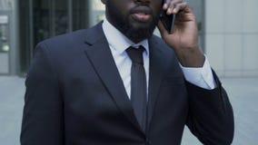 Directeur marchant près du centre d'affaires indiquant ses résultats d'associé des négociations banque de vidéos
