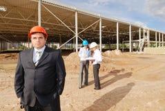 Directeur met ondergeschikten op bouwwerf Stock Foto's