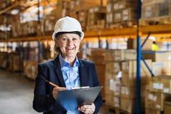 Directeur ou surveillant supérieur d'entrepôt de femme avec le casque et le presse-papiers blancs Photos stock