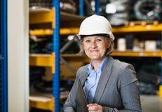 Directeur ou surveillant supérieur d'entrepôt de femme avec le casque et le presse-papiers blancs Photographie stock libre de droits