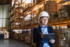 Directeur ou surveillant supérieur d'entrepôt de femme avec le casque et le presse-papiers blancs Photographie stock