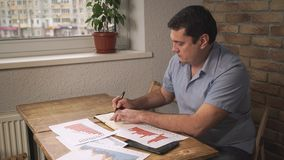 Directeur s'asseyant au bureau, prenant des notes dans un carnet, sur les papiers dispersés par table images libres de droits