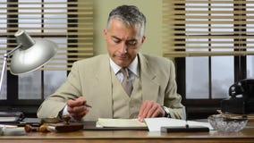 Directeur sûr vérifiant des écritures dans le bureau banque de vidéos