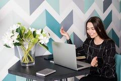 Directeur satisfait de sourire de femme ayant l'appel visuel par l'intermédiaire de l'ordinateur portable, se reposant dans le ca Photographie stock