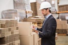Directeur sérieux d'entrepôt vérifiant l'inventaire Photos libres de droits