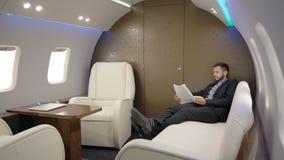 Directeur van de bedrijfseigenaar leest de belangrijkste bankier contract op leerbank van vliegtuig stock videobeelden