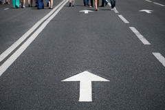 Direction arrow on road and people Royalty Free Stock Images