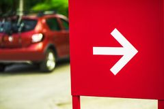 Direction arrow sign with car in background. Direction arrow sign with out of focus car in the background Stock Photos