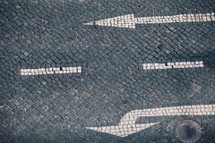 Direction arrow and street sign on handmade stone pavement in Lisbon - Traditional Portuguese handmade mosaic background stock photos