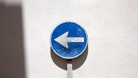 Direction. Blue circle direction arrow sign next to wall Royalty Free Stock Photos