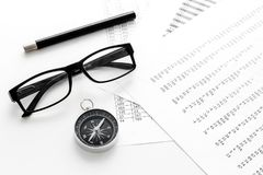 Business development concept. Direction. Compass near documents, glasses, pen on light background top view. Direction of business development concept. Compass Royalty Free Stock Images