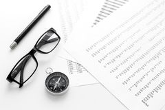 Business development concept. Direction. Compass near documents, glasses, pen on light background top view. Direction of business development concept. Compass Stock Photography