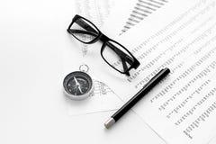 Business development concept. Direction. Compass near documents, glasses, pen on light background top view copy space. Direction of business development concept Stock Image