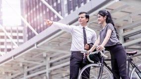 Direction d'homme d'affaires principale pour une femme de sport de bicyclette dans c photographie stock