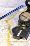 Direction of the journey. Still life with a compass and over a map. the yellow line indicate the route. travel. journey. direction Royalty Free Stock Photo