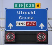Direction and mandatory speed sign above motorway A20 heading to Gouda and Utrecht, also European way E19 and E25. Direction and mandatory speed sign above royalty free stock images