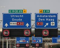 Direction and mandatory speed sign above motorway A20 with split between Rotterdam and to The Hague and Amsterdam via A13.  stock image