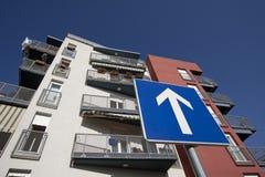 Direction requise de poteau de signalisation devant la façade de bâtiment Images stock