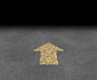 Direction Road Arrow. Direction Arrow on an asphalt street with an old fading yellow painted road symbol pointing into the black blank distant perspective as a Royalty Free Stock Photography