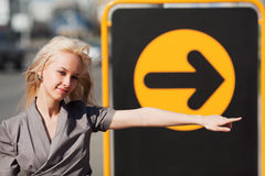 Young woman against direction sign Royalty Free Stock Photo