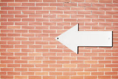 Direction sign on a brick wall Royalty Free Stock Photos