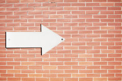 Direction sign on a brick wall Stock Image