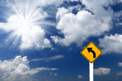 Direction sign- left turn sign. Pointing to rays of light on blue sky background stock image