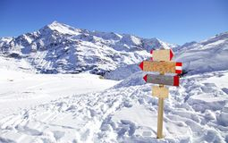 Direction sign at ski resort in the Italian Alps. Winter mountains panorama with wooden sign indicating the path. Abstract concept Stock Photo