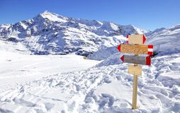 Direction sign at ski resort in the Italian Alps. Winter mountains panorama with wooden sign indicating the path. Abstract concept. ю Royalty Free Stock Photos