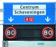 Direction sign with white for local destinations to Center and Scheveningen and mandatory speed limit below it on highway A12 in t royalty free stock images