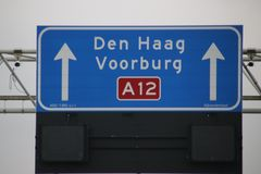 Direction sign with white for local destinations to Den Hag and Voorburg and mandatory speed limit when lit below it on highway A1. 2 in the Netherlands stock image