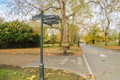 Direction signpost in Hyde Park london with falling trees. In autumn Royalty Free Stock Photo
