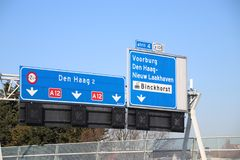 Direction signs above motorway A12 at Prins Clausplein heading Den Haag or The Hague and junction 4 in the Netherlands. Direction signs above motorway A12 at stock photo