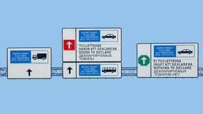 Direction signs follow the type of lane are bi-lingual in English, Russian and Finnish. Isolated on blue sky background. Direction signs follow type of lane are Stock Image