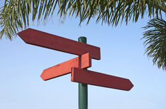 Direction signs in redwood. Pole of three directional signs in redwood under a palm leaf and blue sky as background Stock Image