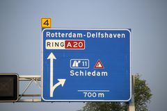Direction and speed sign above motorway A20 with warning for dangerous curve junction to Schiedam. Direction and speed sign above motorway A20 with warning for stock images
