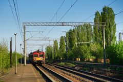 Direction: straight into the light. Red train coming straight. green trees on rails sides. top electric lines. Romanian railways Royalty Free Stock Images
