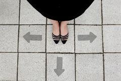 Directional Arrow and Pair of Black Shoes Woman Standing on The Tile Background. Great for Any Use stock photography