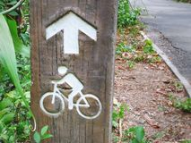 Directional Arrow and Picture Sign of Man Riding Bicycle. Close-up Directional Arrow and Picture Sign of Man Riding Bicycle on a Post by the Road stock image