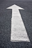 Directional arrow sign on asphalt Stock Images