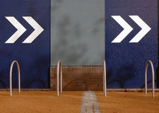 Directional arrows on a blue coloured wall Stock Photos