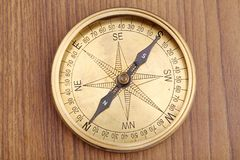 Directional compass. Closeup of old directional compass on a wooden table stock image