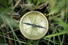 Directional compass in grass Royalty Free Stock Photography