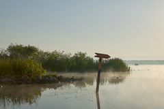 A directional lake channel marker at sunrise. A directional lake channel marker on a beautiful, misty morning with clear blue sky at Lake Panasoffkee in Florida Royalty Free Stock Photo