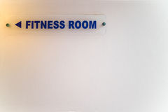 Directional sign to fitness room on white wall. Royalty Free Stock Images
