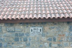 Directional sign to the toilet on the stone wall stock image