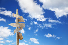 Directional signs blue sky. Directional unfinished wood signs over a blue sky royalty free stock image