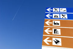 Directional signs with symbols. A picture of some blue and white directional signs with icons printed on them, indicating places of interest to tourists Stock Photos