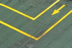 Directional traffic yellow arrow on a green tarmac texture floor. stock image