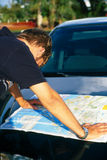 Directions. Man looking at a map on hood of car Royalty Free Stock Photo